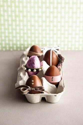 Huevos de chocolate de pascua dispuestos en un cartón huevera tradicional