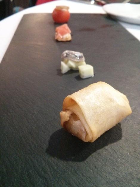 Plato de entrantes compuesto por tomate relleno de crema de queso con frutos secos, sardina marinada con ensalada de pepino, blinis de salmón con encurtidos y rollito de primavera Kaymus