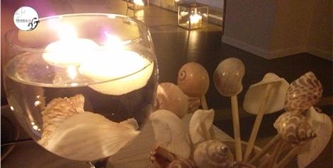 Decoración con velas y caracolas en la mesa